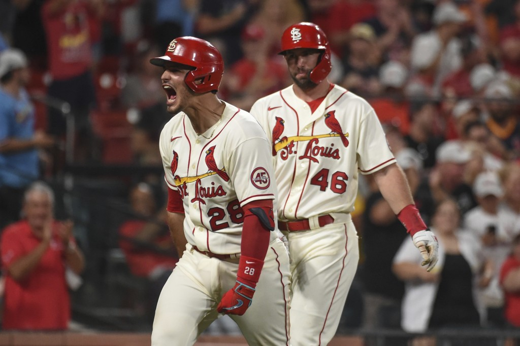 St. Louis Cardinals' Nolan Arenado, left, reacts after hitting a two-run home run during the eighth inning of a baseball game against the Cincinnati R...