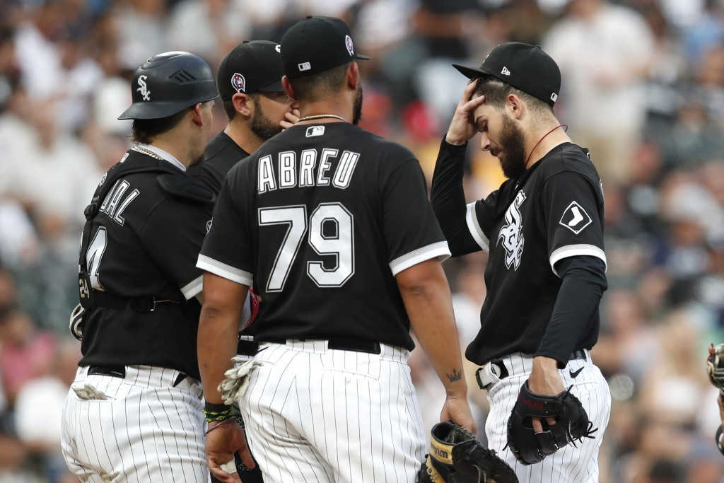 Chicago White Sox starting pitcher Dylan Cease, right, reacts after walking two Boston Red Sox batters during the first inning of baseball game, Satur...