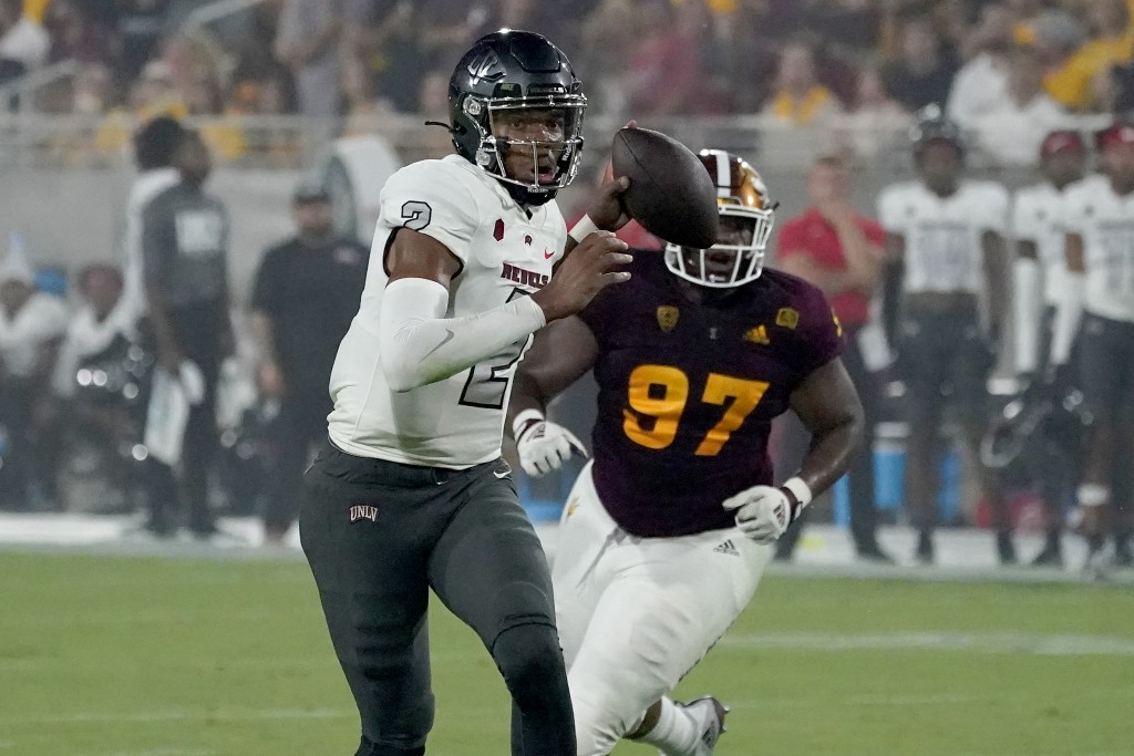 UNLV quarterback Doug Brumfield (2) scrambles as Arizona State defensive lineman Shannon Forman (97) pursues during the first half of an NCAA college ...
