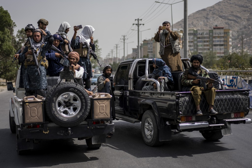 Taliban fighters escort women's march in support of the Taliban government outside Kabul University, Afghanistan, on Saturday, Sept. 11, 2021. (AP Pho...