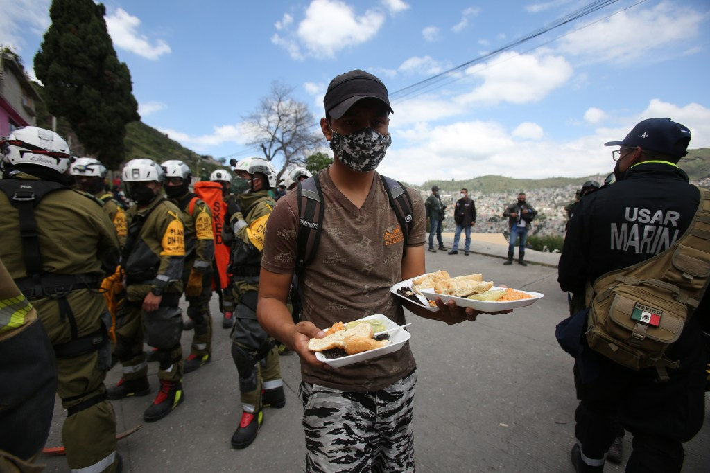 A volunteer offers plates of food to soldiers working in the search and rescue efforts at the site of a landslide that brought tons of massive boulder...