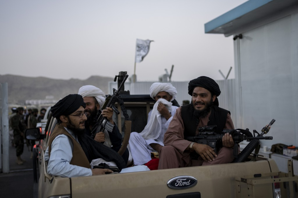 Taliban fighters sit in a pickup truck at the airport in Kabul, Afghanistan, Thursday, Sept. 9, 2021. Some 200 foreigners, including Americans, flew o...