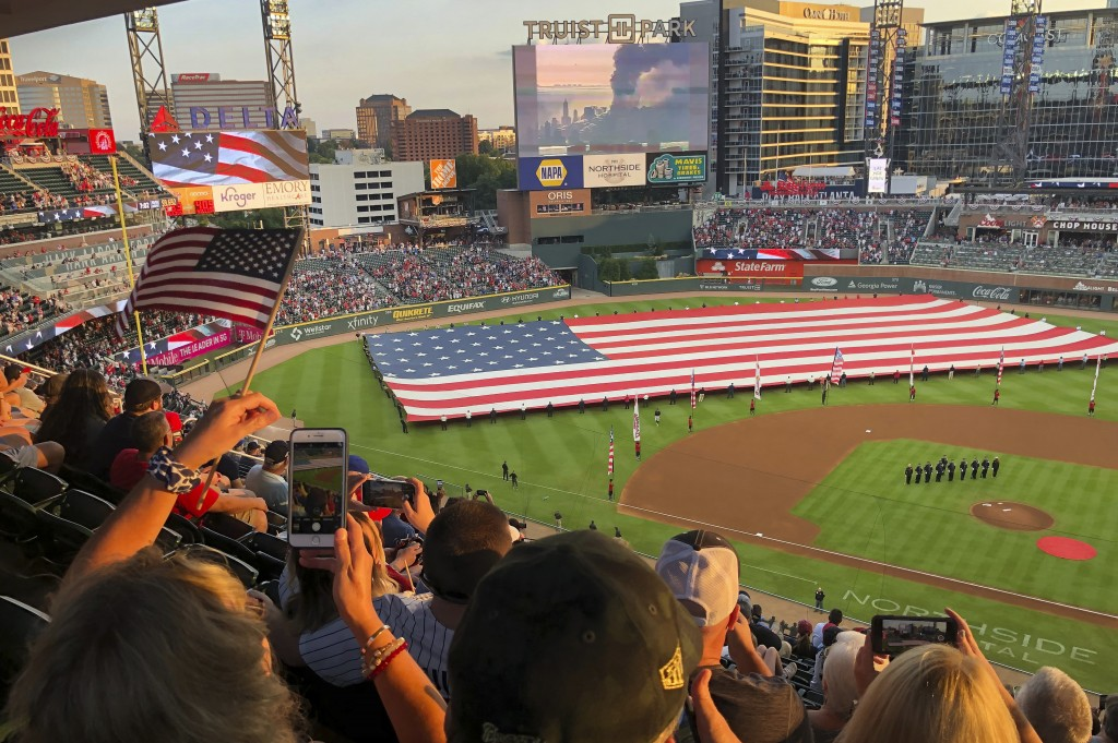 Fans take photos during a pre-game ceremony in remembrance of the 9/11 attacks prior to a baseball game between the Atlanta Braves and the Miami Marli...