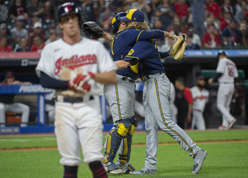 Milwaukee Brewers relief pitcher Josh Hader right, hugs catcher Omar Narvaez as Cleveland Indians' Myles Straw walks off the field after the final out...