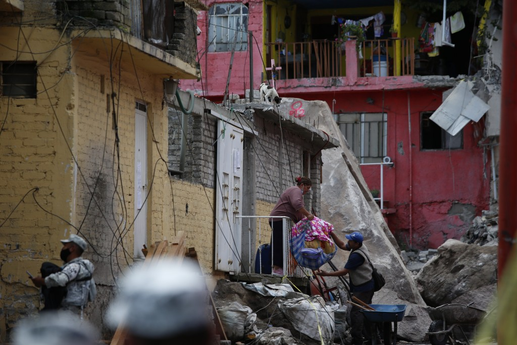 Residents evacuate from their home at the site of a landslide that brought tons of massive boulders down on a steep hillside neighborhood, in Tlalnepa...