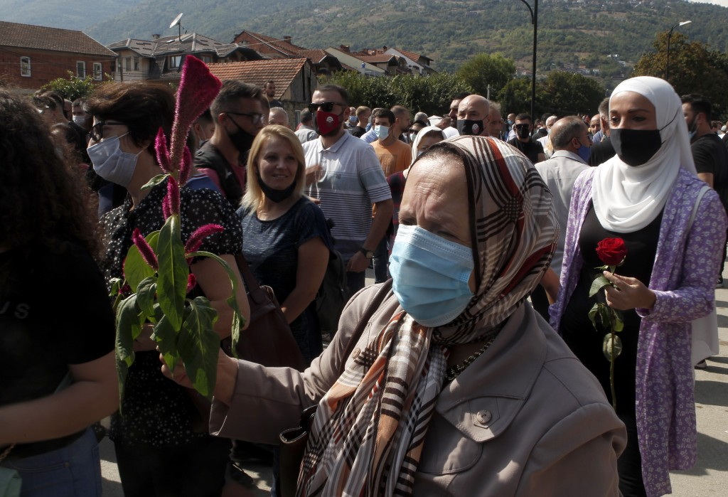 Women carry flowers to honor the victims in the burned out makeshift hospital in North Macedonia's northwestern town of Tetovo, Saturday, Sept. 11, 20...