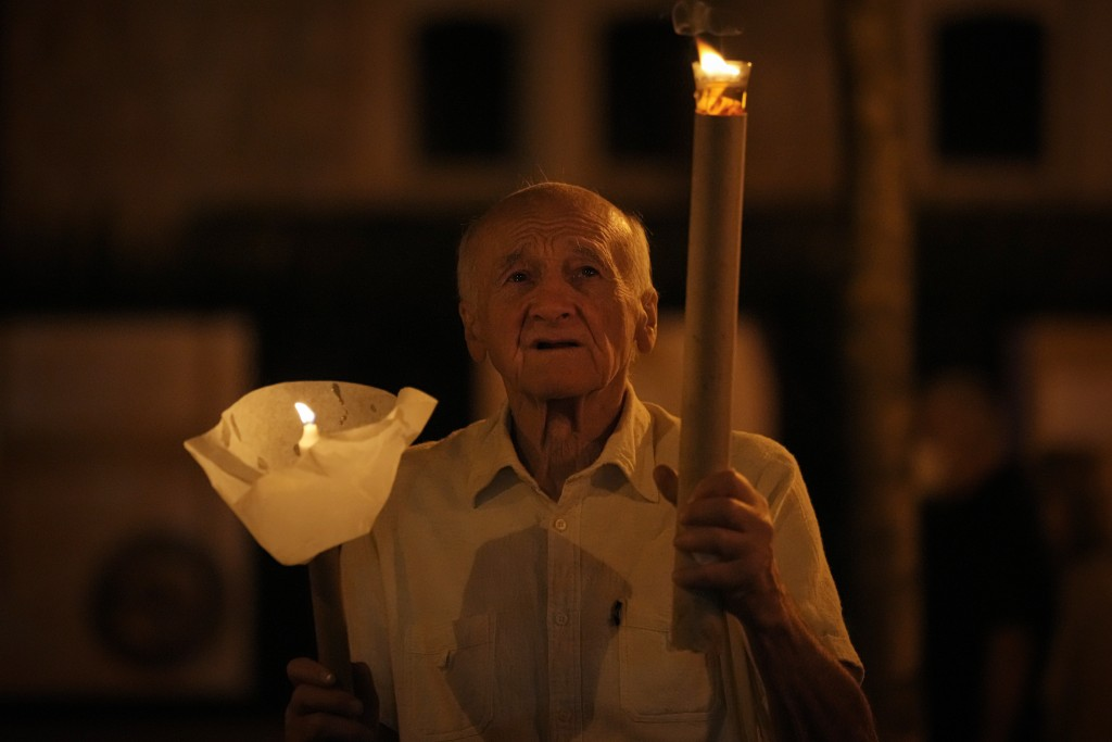 A man holds a torch during a procession joined by tens of thousands in Budapest, Hungary, Saturday, Sept. 11, 2021, the day before the final mass of I...