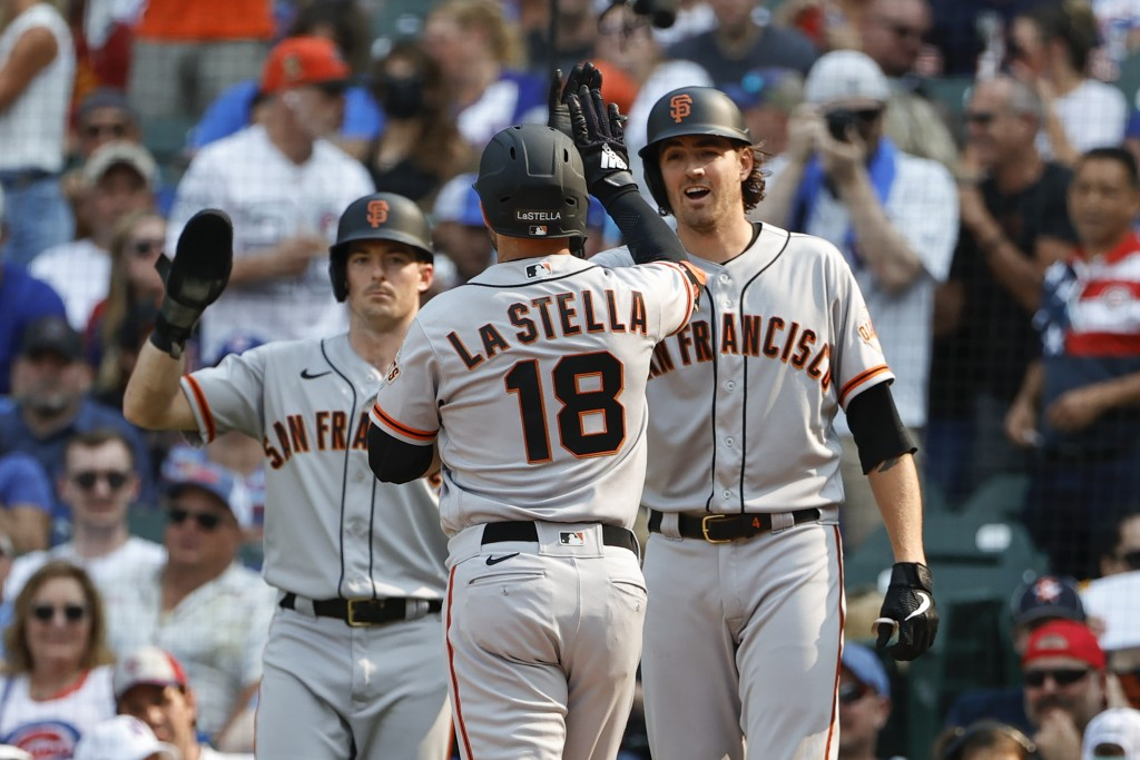 San Francisco Giants' Tommy La Stella, center, celebrates with Mike Yastrzemski, left, and Kevin Gausman, right, as he crosses home plate after hittin...