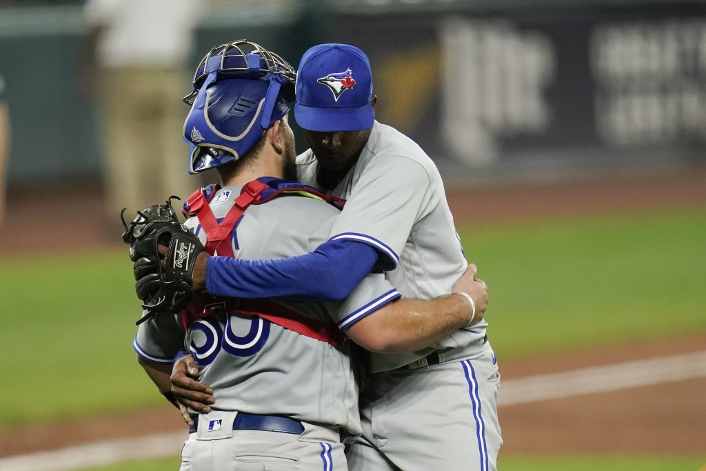 Toronto Blue Jays catcher Alejandro Kirk, left, and relief pitcher Anthony Castro embrace after defeating the Baltimore Orioles during the second game...