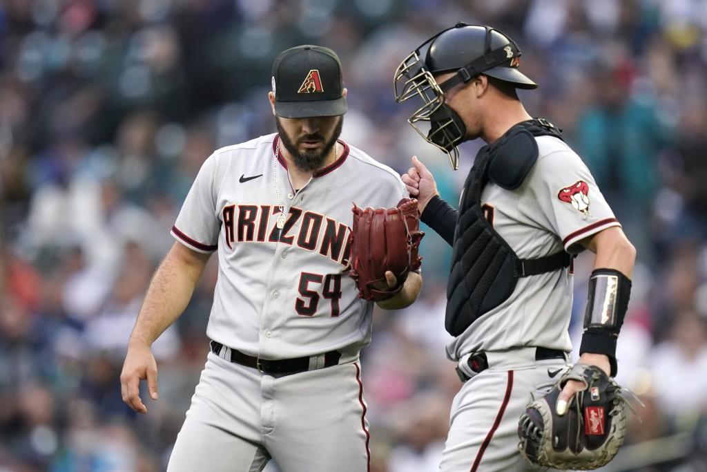 Arizona Diamondbacks starting pitcher Humberto Castellanos, left, talks with catcher Carson Kelly during the the first inning of the team's baseball g...