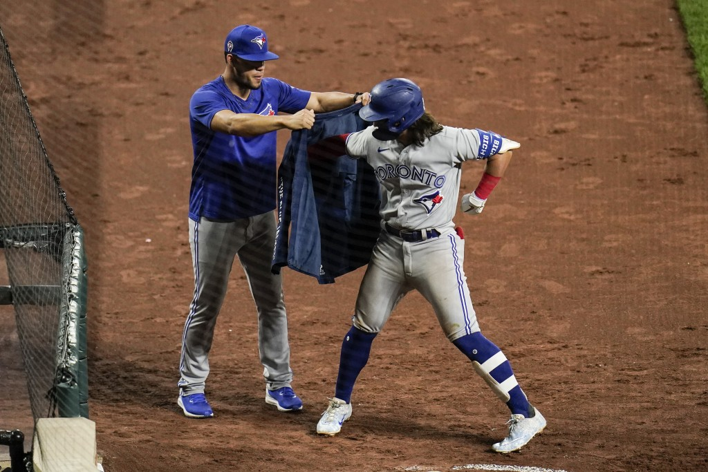 Toronto Blue Jays' Bo Bichette, right, is helped to put on a blazer by pitcher Jose Berrios after hitting a two-run home run off Baltimore Orioles sta...