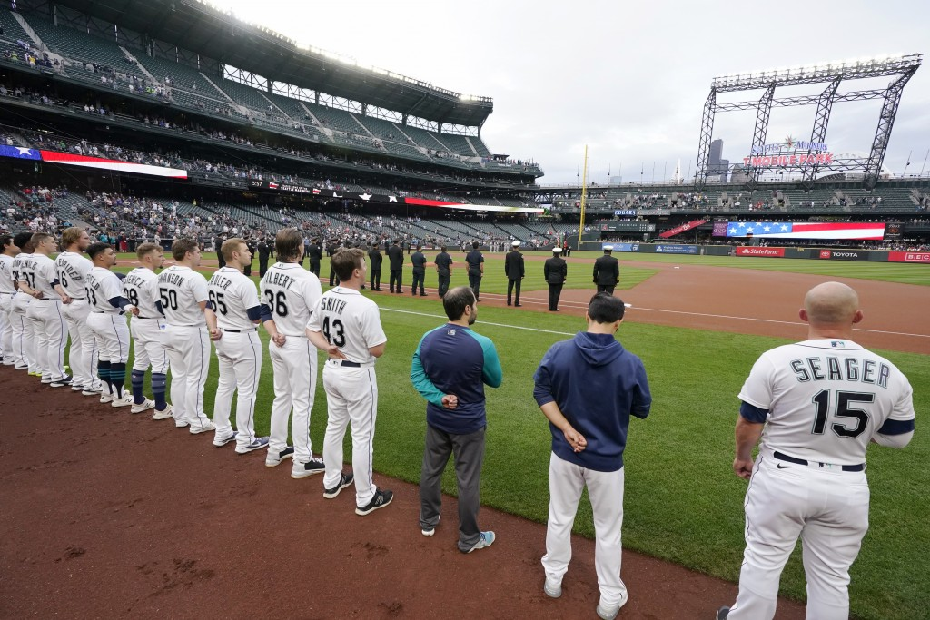 Seattle Mariners players stand near the dugout as first responders stand along the first base line as the team commemorates the 20th anniversary of th...