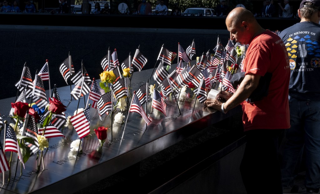 Flags and flowers adorn the names of the victims of the attacks of Sept. 11, 2001, at the National September 11 Memorial in New York on the 20th anniv...
