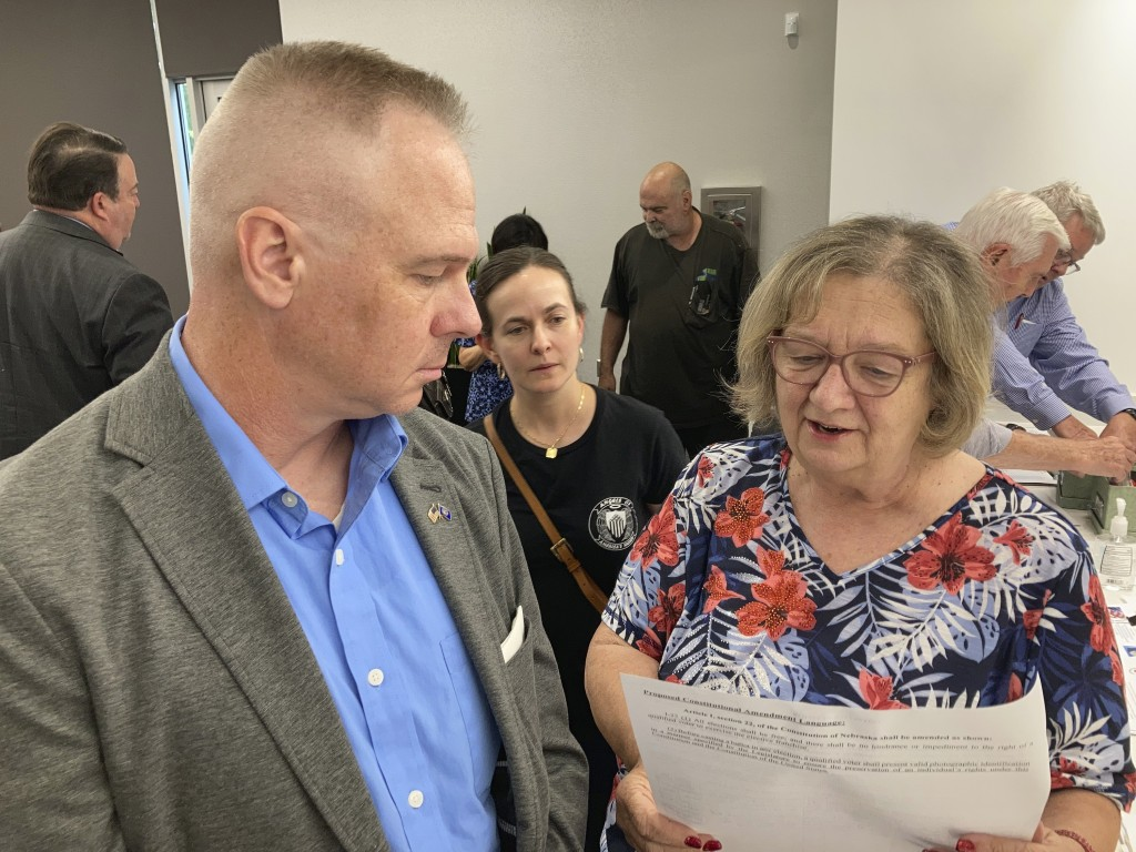 Brian Stransky, of unincorporated Sarpy County, Nebraska, listens as Citizens for Voter ID campaign official Nancy McCabe reads to him from a voter ID...