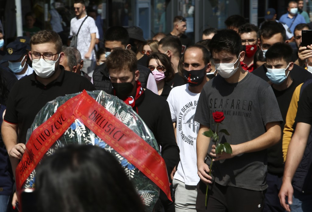Young men carry a wreath and flowers while marching in silence to honor the victims in the burned out makeshift hospital in North Macedonia's northwes...