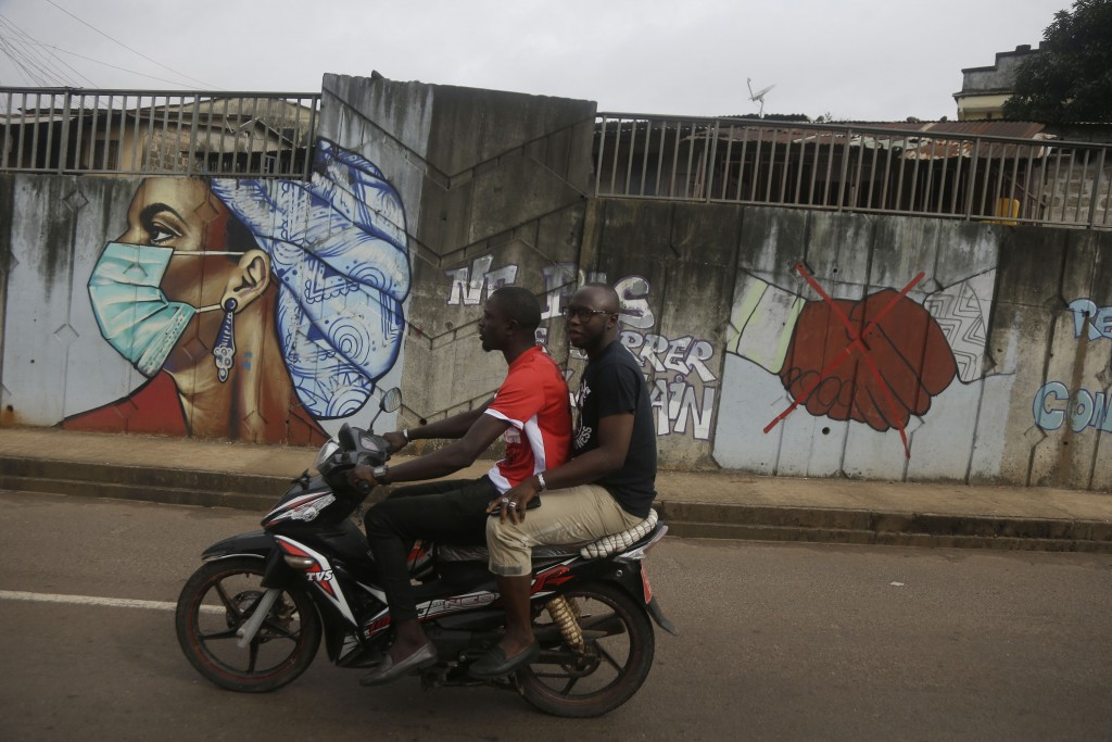 People ride on a motorbike past graffiti on measures how to prevent contracting the COVID-19 virus in Conakry, Guinea Friday, Sept. 10, 2021. (AP Phot...