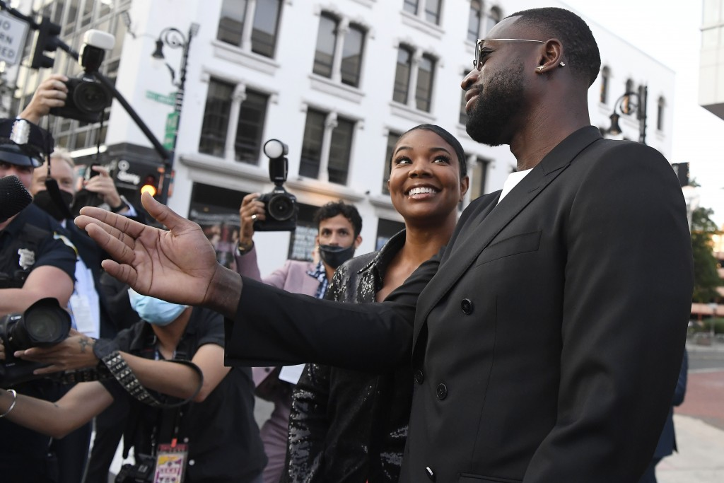 Dwyane Wade and Gabrielle Union greet fans as they arrive for the 2021 Basketball Hall of Fame Enshrinement ceremony, Saturday, Sept. 11, 2021, in Spr...