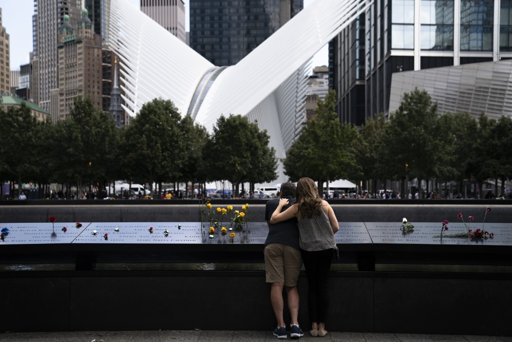 Mourners stand at the rim of the north pool with the white World Trade Center Oculus in the background after the conclusion of ceremonies to commemora...