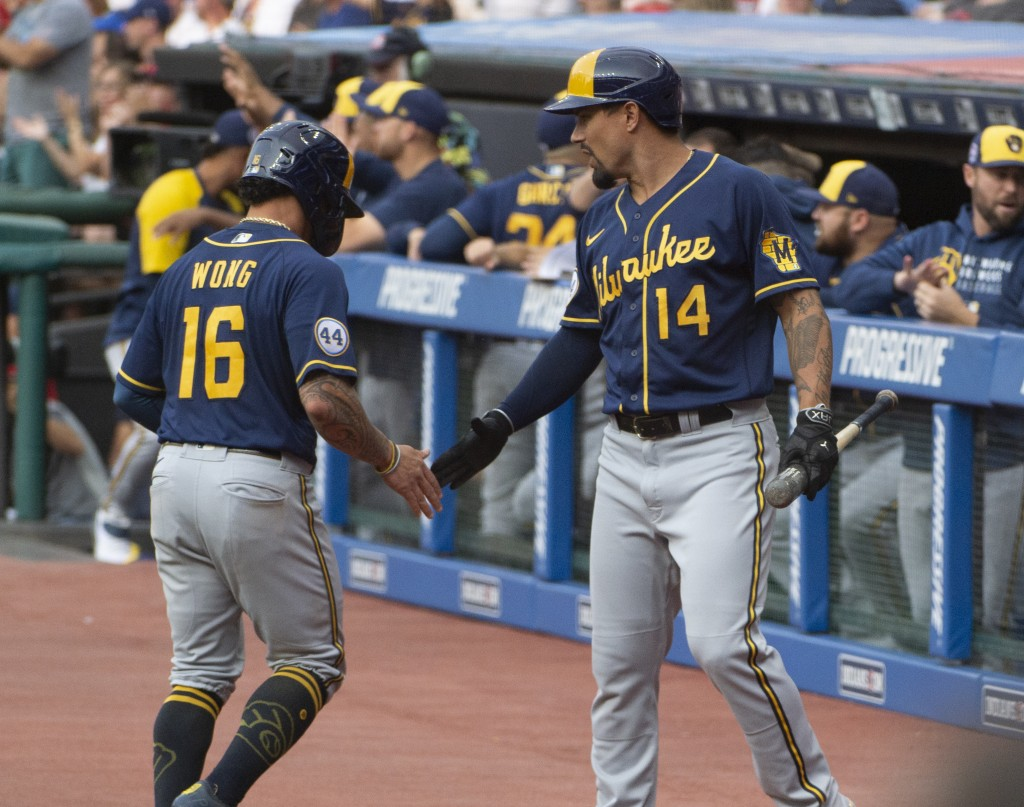 Milwaukee Brewers' Jace Peterson (14) congratulates Kolten Wong for scoring on a triple by Christian Yelich during the first inning of a baseball game...