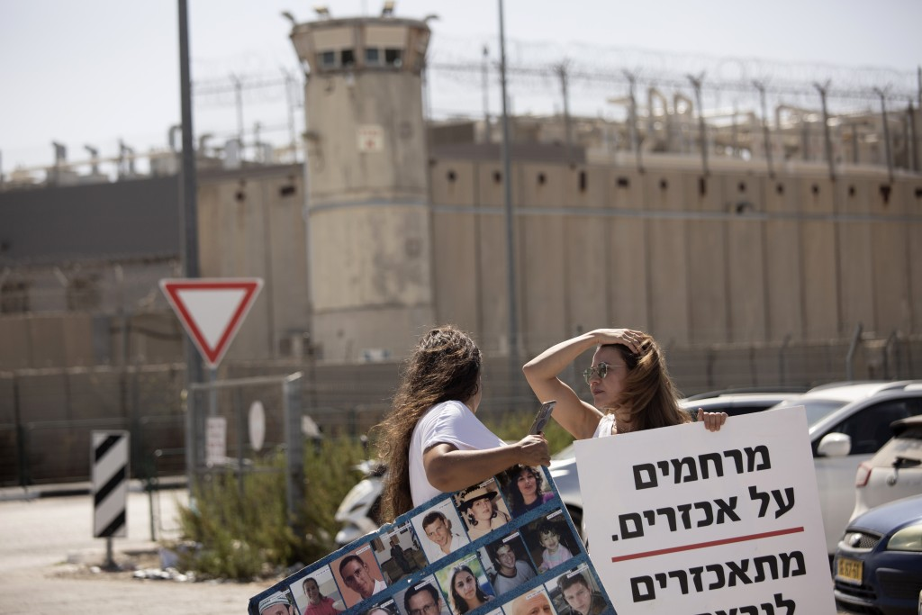 Members of the group Choosing Life, that includes relatives of Israelis killed in Palestinian attacks, protest outside of Ofer Prison near Jerusalem, ...