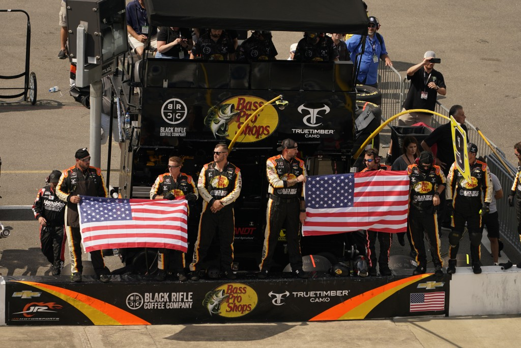 The pit crew of Noah Gragson (9) displays the U.S. flag during laps nine, ten and eleven during the NASCAR Xfinity auto race in Richmond, Va., Saturda...