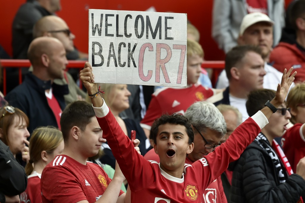 A fan holds up a sign for Manchester United's Cristiano Ronaldo during the players' warmup before the English Premier League soccer match between Manc...