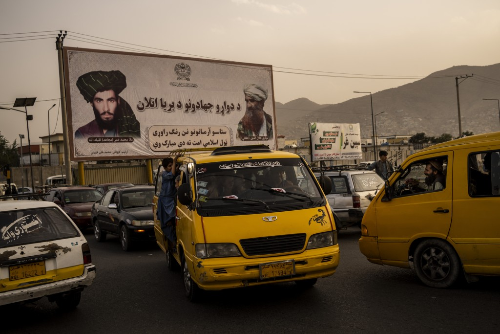 Vehicles drive past a mural paying homage to late Taliban founder Mullah Mohammad Omar, left, and the late founder of the feared Haqqani network, Jala...