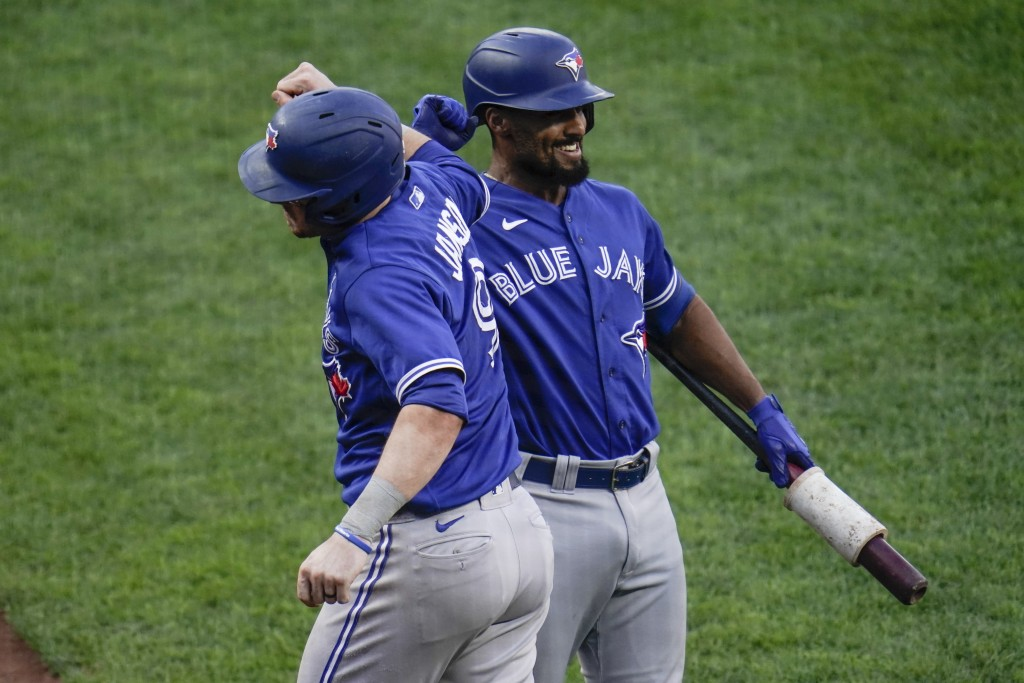 Toronto Blue Jays' Danny Jansen, left, is congratulated by Marcus Semien after hitting a two-run home run against the Baltimore Orioles during the fou...