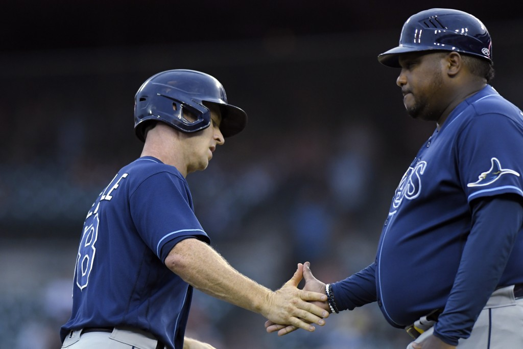 Tampa Bay Rays' Joey Wendle, left, is congratulated by third base coach Rodney Linares after hitting a home run off Detroit Tigers pitcher Bryan Garci...