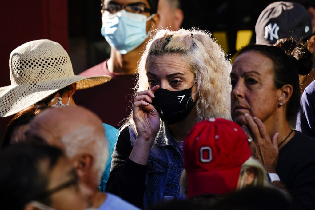 A person wipes her eye as she gathers with others outside the National September 11 Memorial and Museum during a ceremony marking the 20th anniversary...