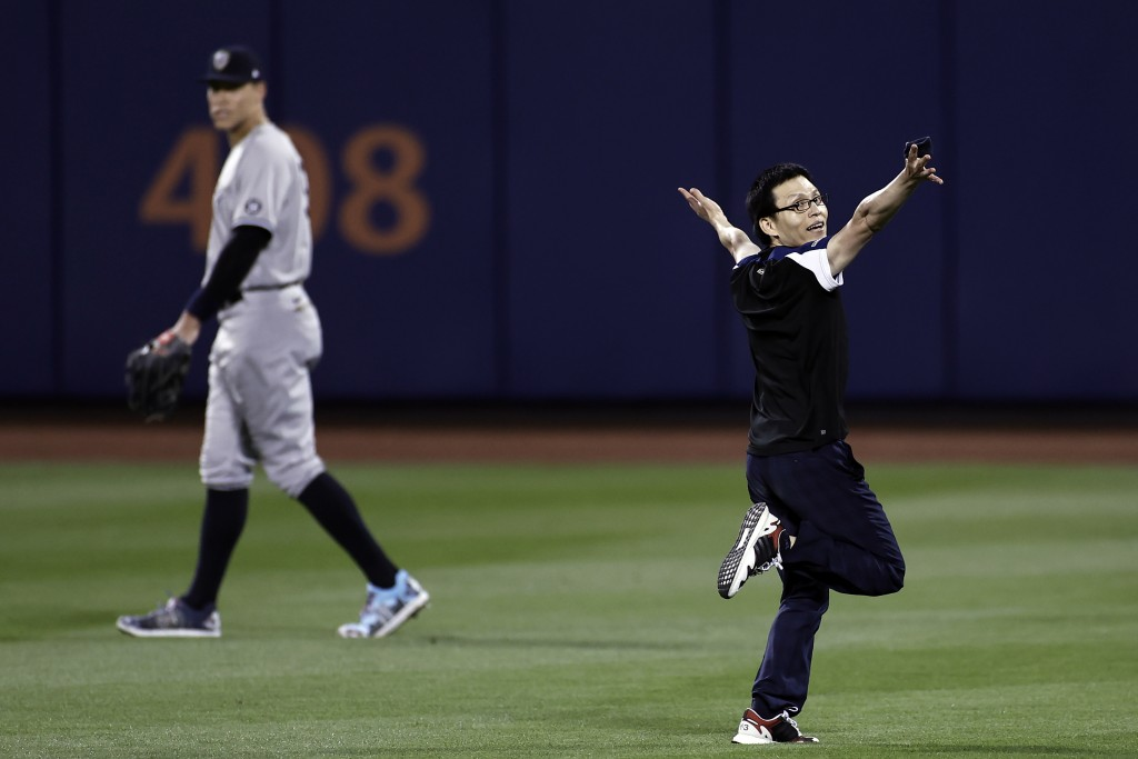 A fan, right, runs on the field past New York Yankees right fielder Aaron Judge during the sixth inning of a baseball game against the New York Mets o...