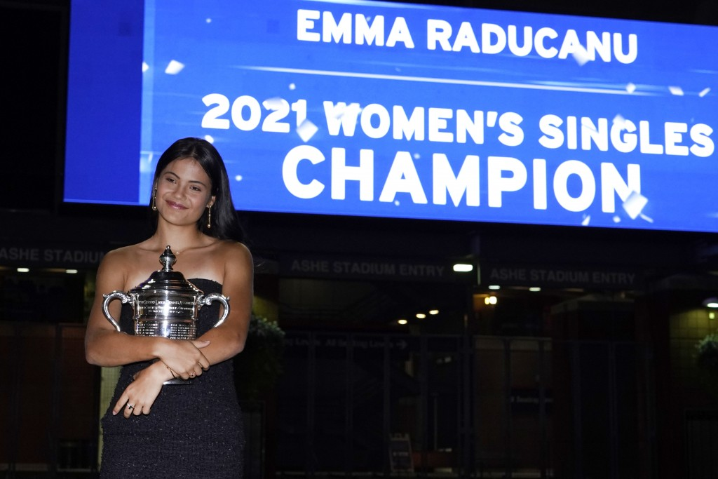 Emma Raducanu, of Britain, poses outside Arthur Ashe Stadium with the championship trophy after she defeated Leylah Fernandez, of Canada, in the women...