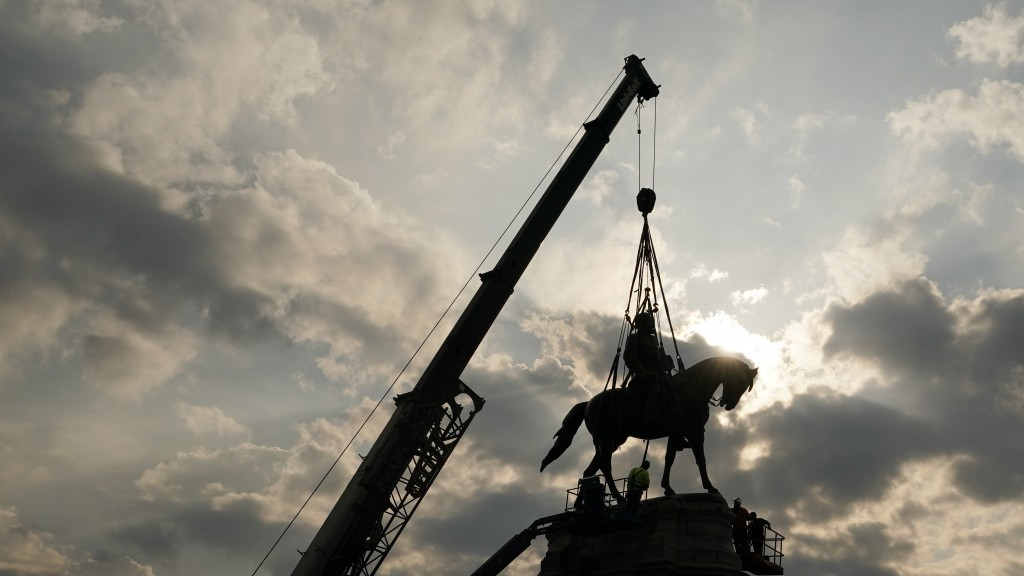 Crews work to remove one of the country's largest remaining monuments to the Confederacy, a towering statue of Confederate Gen. Robert E. Lee on Monum...