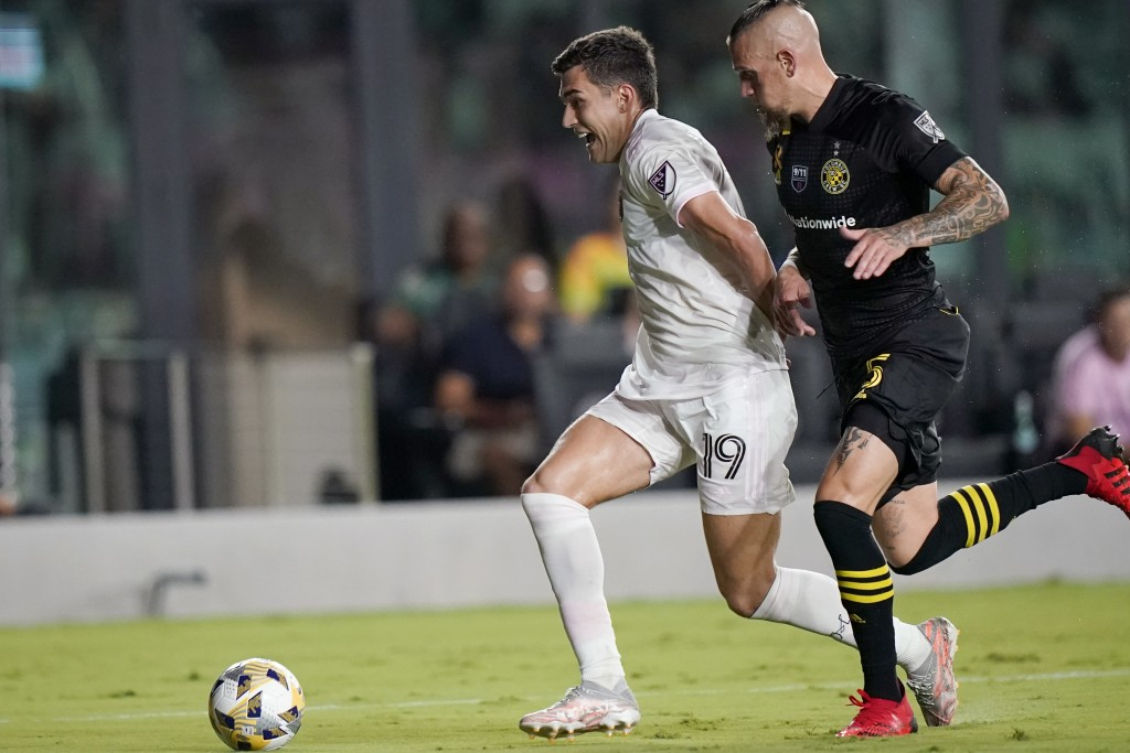 Inter Miami forward Robbie Robinson (19) runs with the ball as Columbus Crew defender Vito Wormgoor pursues during the second half of an MLS soccer ma...