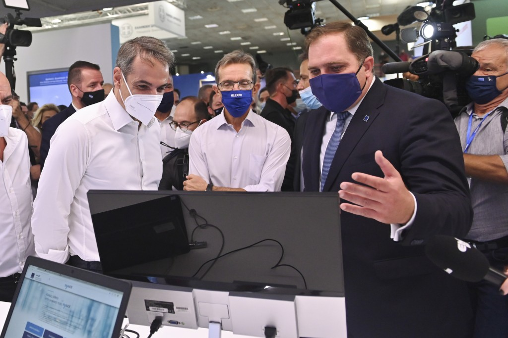 Greece's Prime Minister Kyriakos Mitsotakis, left, reacts as he looks at a computer monitor during a tour of Thessaloniki International Trade Fair, in...