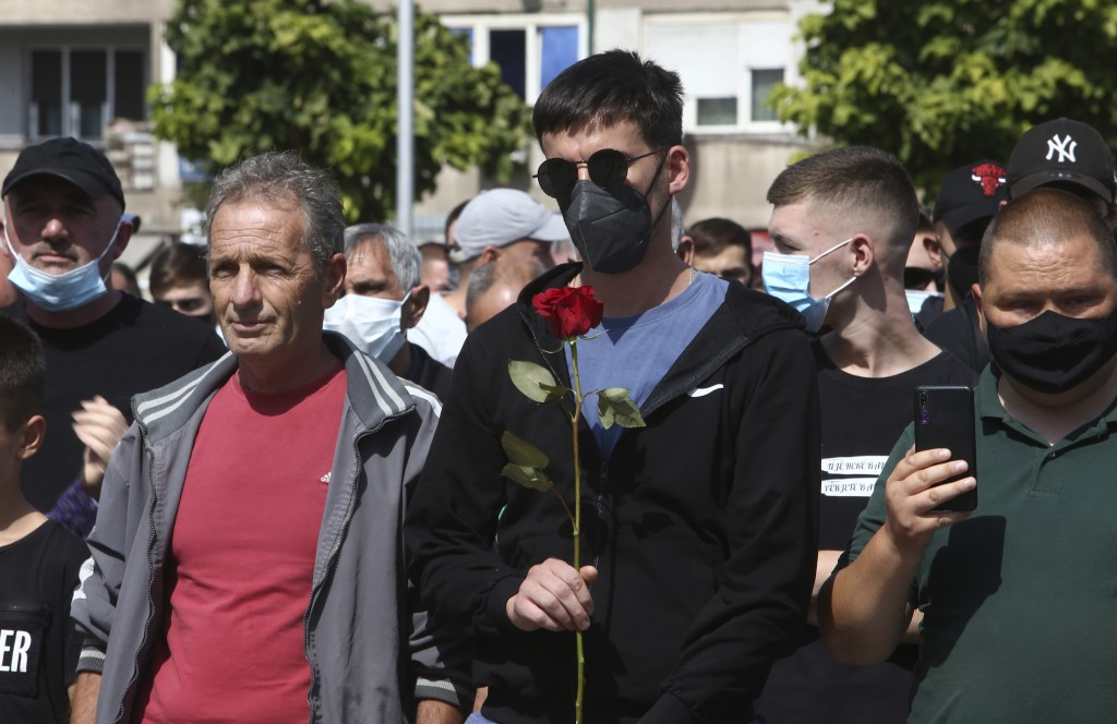 A young man holds a rose during a march to honor the victims in the burned out makeshift hospital in North Macedonia's northwestern town of Tetovo, Sa...