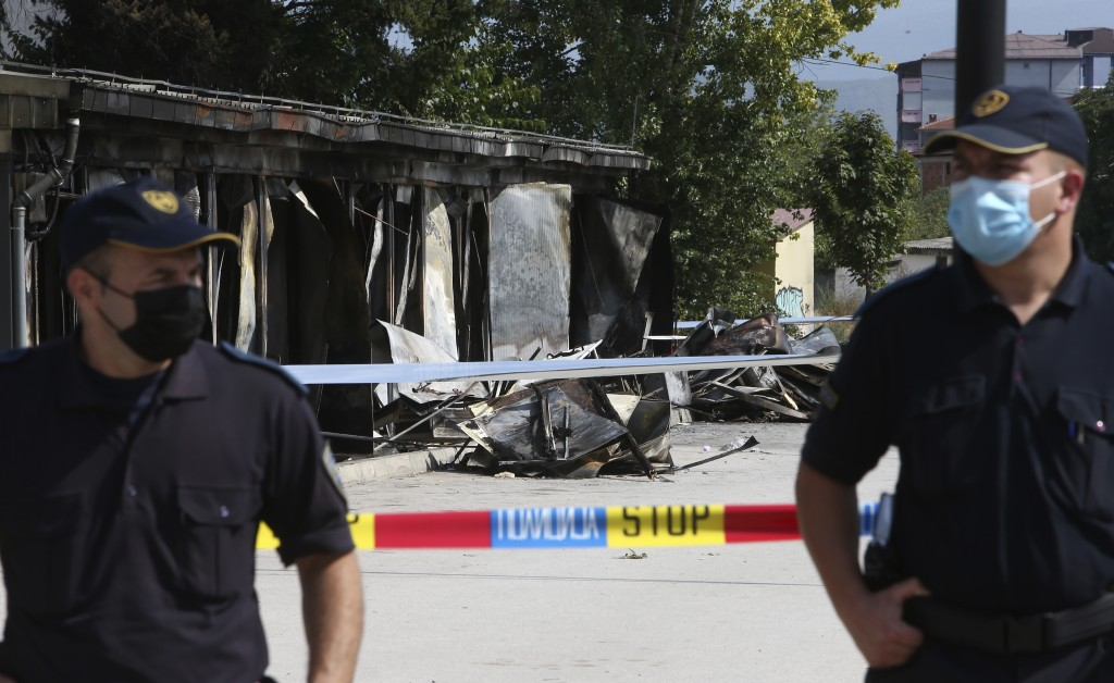Police officers guard the access to the burned out makeshift hospital, in North Macedonia's northwestern town of Tetovo, Saturday, Sept. 11, 2021. Hun...
