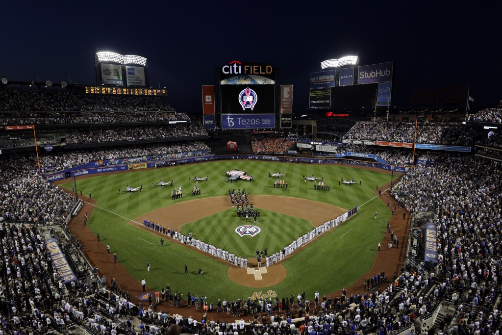 The New York Yankees and the New York Mets line up together along the baselines for the 20th anniversary of the 9/11 terrorist attacks before a baseba...