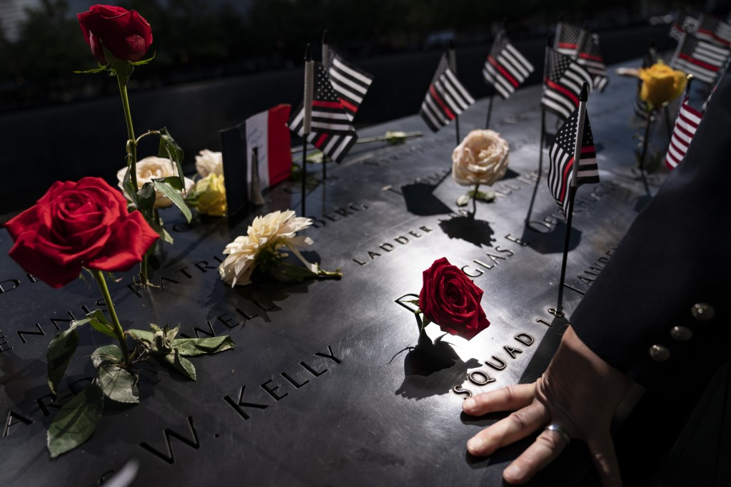 A firefighter places his hand on the name engravings on the south pool during ceremonies to commemorate the 20th anniversary of the Sept. 11 terrorist...