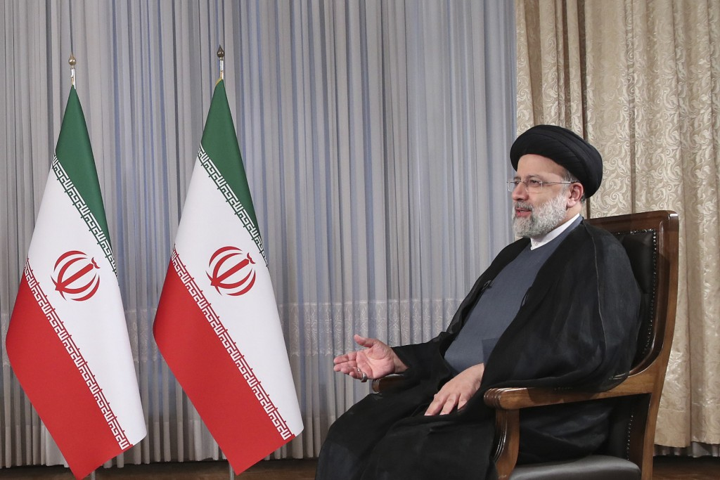 In this photo released by the official website of the office of the Iranian Presidency, President Ebrahim Raisi speaks in a live televised interview w...