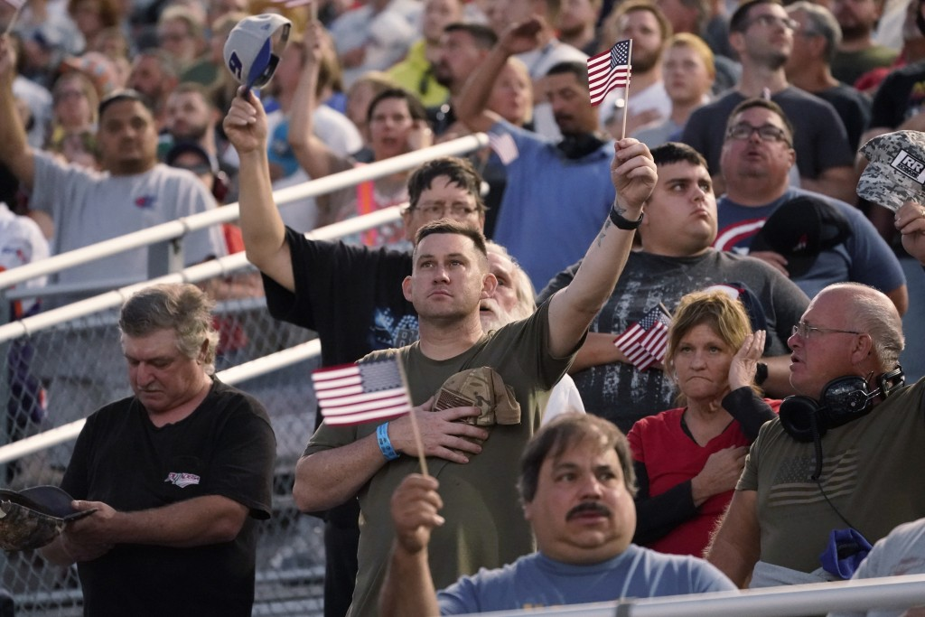 Race fans hold U.S. flags during the singing of the national anthem before the NASCAR Cup series auto race in Richmond, Va., Saturday, Sept. 11, 2021....
