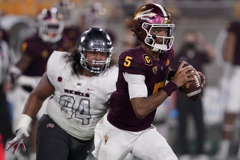 Arizona State quarterback Jayden Daniels (5) looks to throw as UNLV defensive lineman Kolo Uasike (94) pursues during the first half of an NCAA colleg...