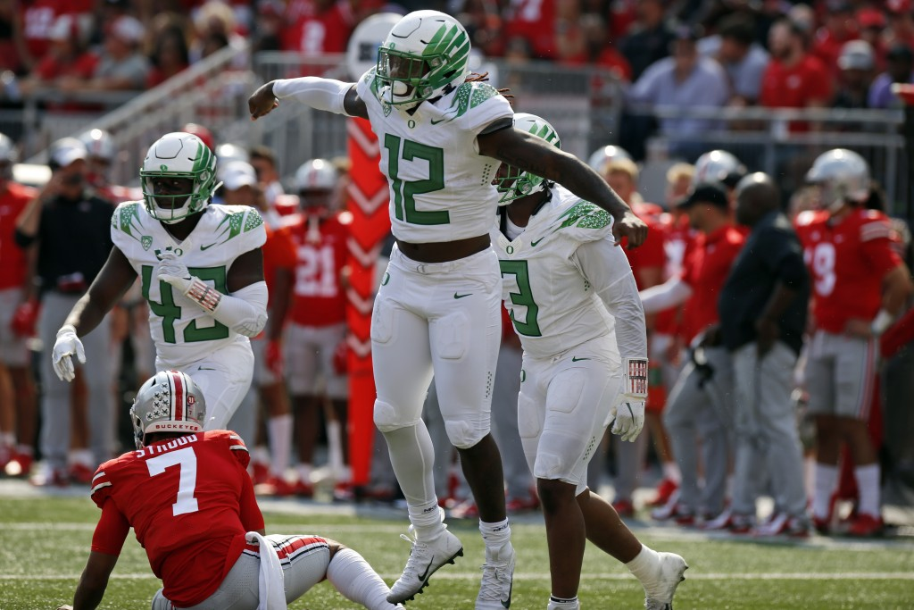 Oregon defensive end DJ Johnson, front, celebrates his sack of Ohio State quarterback C.J. Stroud on the final play of the game in the second half of ...