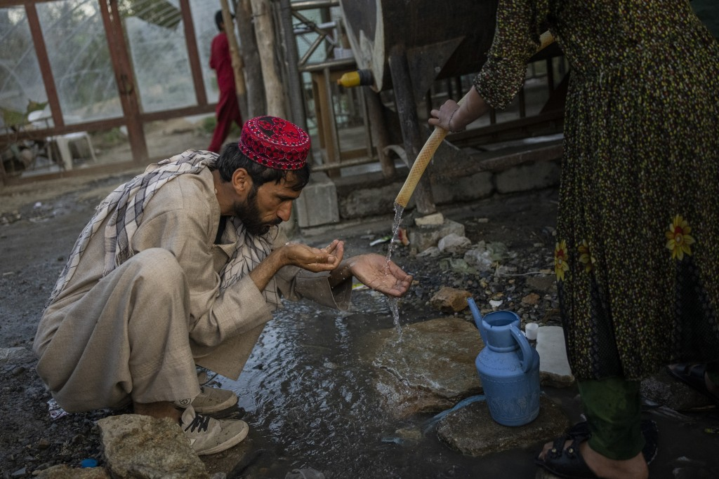 A displaced Afghan man drinks from a water tank at an internally displaced persons camp in Kabul, Afghanistan, Monday, Sept. 13, 2021. (AP Photo/Berna...