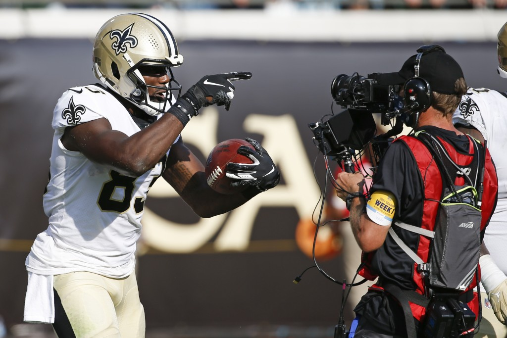 New Orleans Saints tight end Juwan Johnson, left, celebrates his touchdown reception against the Green Bay Packers as he points to a TV cameraman duri...