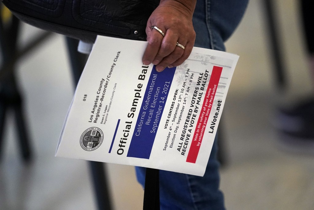 FILE — In this Sept. 7, 2021 file photo a voter holds a sample ballot while casting an early ballot for the California gubernatorial recall election a...
