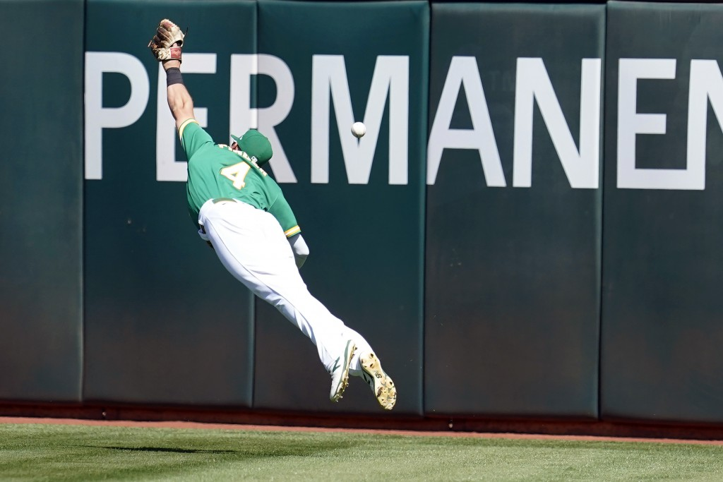 Oakland Athletics right fielder Chad Pinder cannot catch an RBI-triple by Texas Rangers' Leody Taveras during the fourth inning of a baseball game in ...