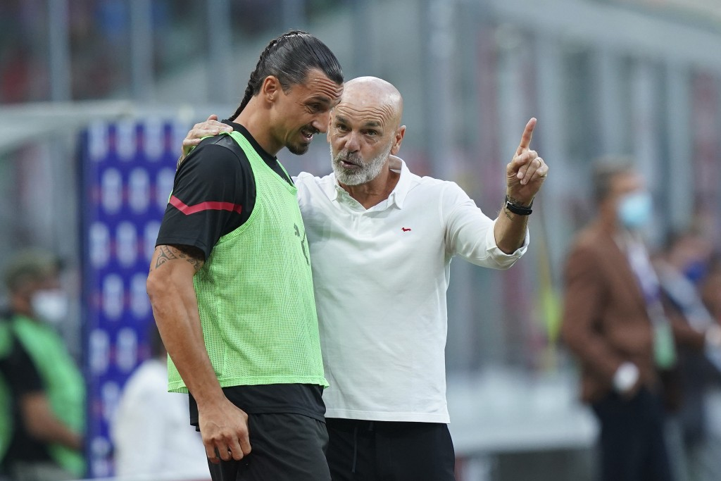Milan's Zlatan Ibrahimovic talks with coach Stefano Pioli before entering the field and scoring  his side's second goal during the Italian Serie A soc...