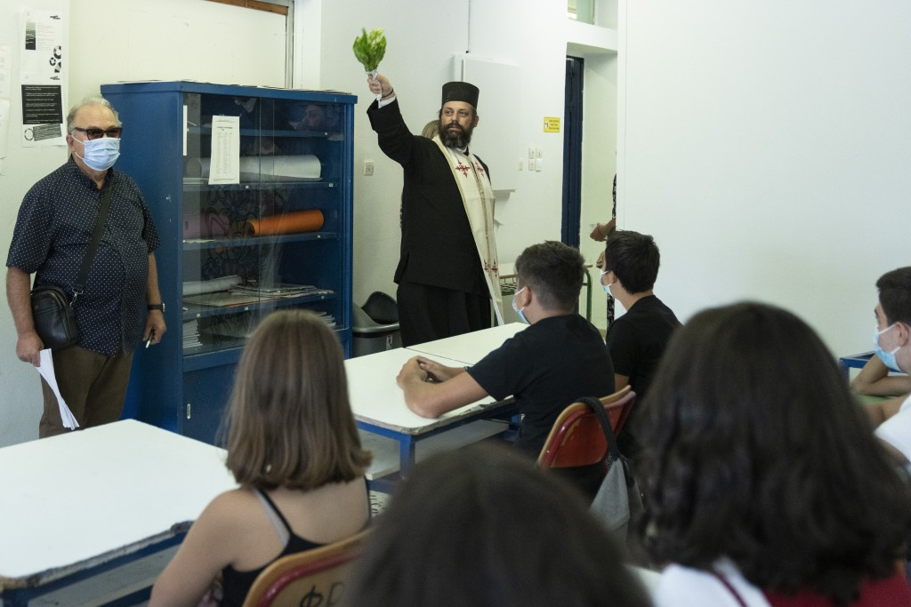 A Greek Orthodox priest blesses students in a classroom of a junior high school in Athens, Monday, Sept. 13, 2021. Public and private sector employees...