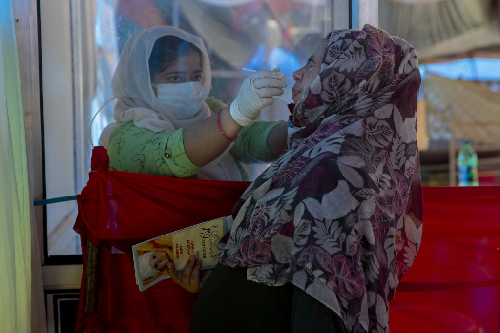 A health worker takes a nasal swab sample of a Kashmiri woman to test for COVID-19 in Srinagar, Indian controlled Kashmir, Tuesday, Sept.14, 2021. (AP...